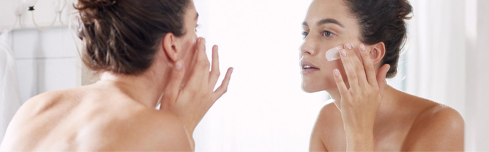 Woman moisturising herface